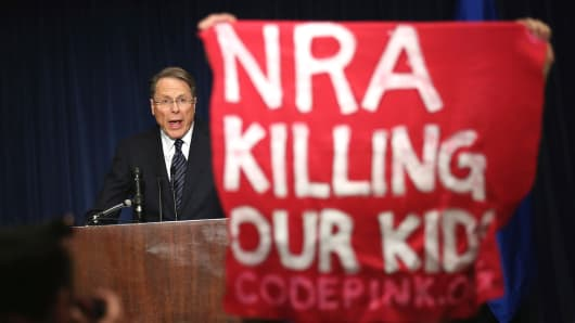 A demonstrator from CodePink holds up a banner as National Rifle Association Executive Vice President Wayne LaPierre delivers remarks during a news conference.