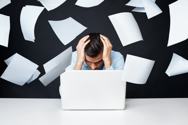 stressed out man hunched over his computer