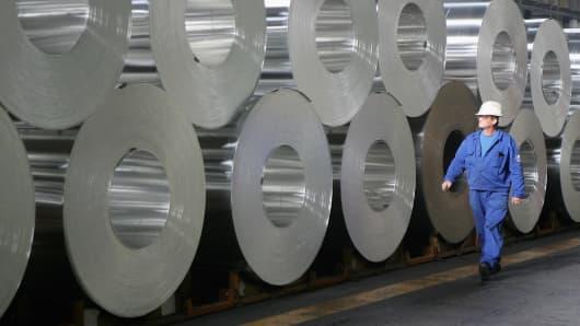 A worker walks among rolls of semi-finished aluminum at an Alcoa aluminum factory.