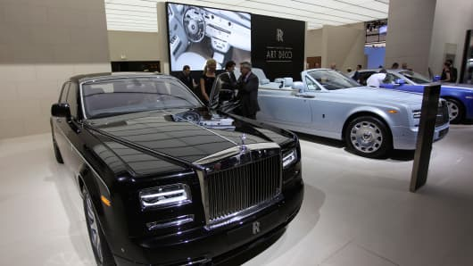 Visitors look at a Rolls-Royce Phantom luxury automobile.