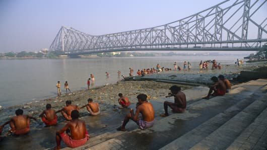 Morning bathers  by the Hooghly River with the massive outline of Howrah Bridge filling the skyline in Kolkata, India.