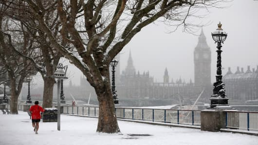 A man runs along the South Bank of the river Thames as snow falls on January 18, 2013 in London, England.