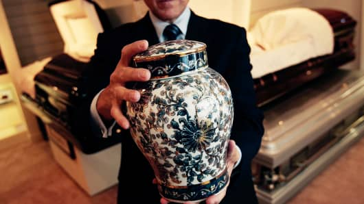 A funeral director of Greenwich Village Funeral Home, holds a cremation urn in the showroom of his funeral parlor in New York City.