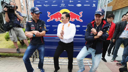 Korean rapper Psy (C) teaches Red Bull Racing drivers Mark Webber (L) and Sebastian Vettel (R) the Gangnam Style dance before the Korean Formula One Grand Prix at the Korea International Circuit on October 14, 2012 in Yeongam-gun, South Korea.