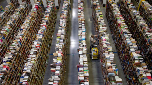 An employee collects merchandise ordered by customers for shipment from the Amazon.com distribution center.