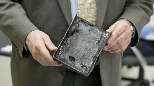 Joseph Kolly, Director of research and engineering with the National Transportation Safety Board holds a damaged battery cell case from a Japan Airlines Co. (JAL) Boeing Co. 787 Dreamliner at the NTSB materials laboratory in Washington, D.C.