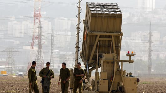 Israeli soldiers stand next to an 'Iron Dome' short-range missile defense system near Haifa.