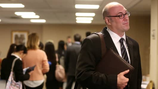 An applicant stands after meeting potential employers at a job fair in New York.