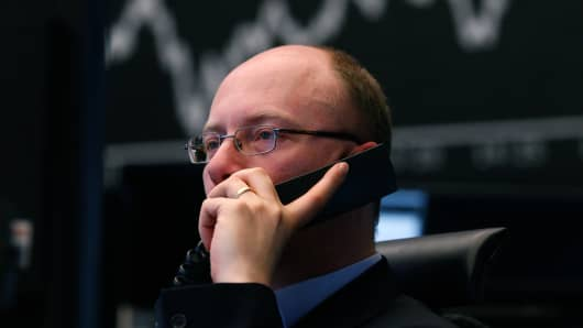 A financial trader uses a telephone as he monitors data on his computer screens in front of a display of the DAX Index curve at the Frankfurt Stock Exchange.