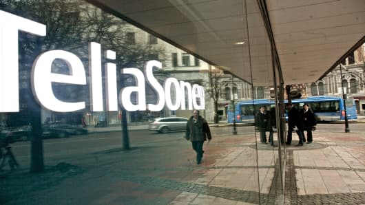 Pedestrians pass the TeliaSonera AB company headquarters in Stockholm, Sweden.