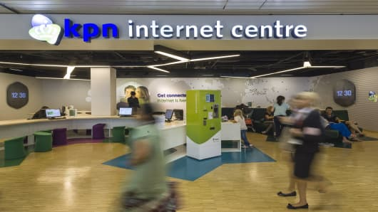 Passengers pass a Royal KPN NV internet centre at Schiphol airport in Amsterdam, Netherlands.