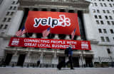 Yelp Inc. signage hangs outside of the New York Stock Exchange (NYSE) in New York, U.S., on Friday, March 2, 2012.