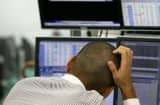 A trader monitors the foreign exchange and stocks index in Tokyo.