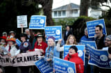 Protesters chant outside Mark Zuckerberg&#039;s Silicon Valley home, where he hosted a fundraiser for Gov. Chris Christie.
