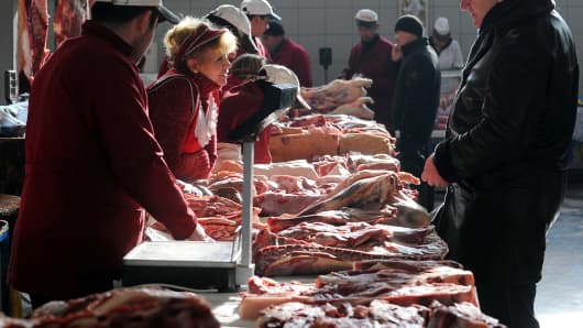 A man buys meat at a butcher's stand in Moscow's Dorogomilovsky market.