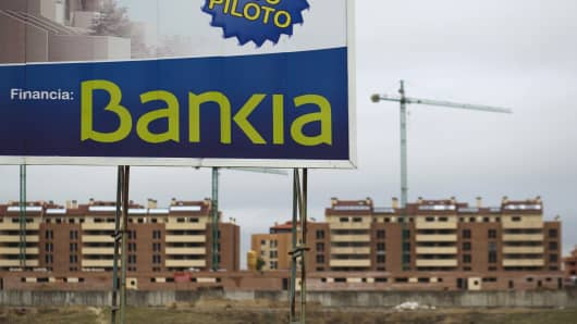 "A sign reading ""Visit our pilot housing, funded by Bankia"" stands near new residential apartment blocks under construction in Navalcarnero, near Madrid, Spain."