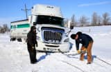 Tow truck driver Tyson House helps trucker Gary Wheeler of Kansas City after his truck slid off the road during large midwest winter storm which brought snow throughout the region on February 22, 2013 in Greensburg, Kansas.