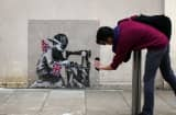 A man takes a phone photo of an artwork attributed to Banksy on May 17, 2012 in London, England.