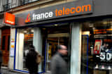Pedestrians pass a France Telecom shop in central Paris