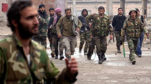 Syrian regime forces take position outside a cement factory following clashes with rebels in the strategic district of Sheikh Said in the northern city of Aleppo on February 3, 2013.