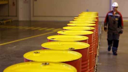 An employee walks past a conveyor belt carrying barrels at a Royal Dutch Shell processing plant.