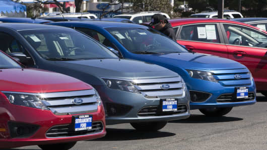 A customer looks over a Ford Fusion parked on the lot at a dealership in Colma, Calif.