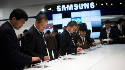 Visitors look at new Samsung devices during the first day of the Mobile World Congress 2013.