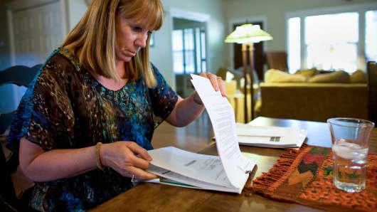 A woman looks through mortgage paperwork in her home in Boise, Idaho.