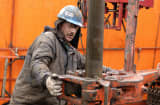 A worker positions a tool on a length of pipe while changing a tool on the drill on a Chief Oil and Gas, LLC natural gas rig in Mifflin Township, Pennsylvania.