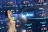 A Nasdaq television reporter is seen inside the Nasdaq studios as the Facebook logo is displayed on a ticker board.
