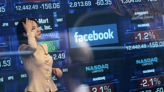 A television reporter is seen inside the Nasdaq studios as the Facebook logo is displayed on a ticker board.
