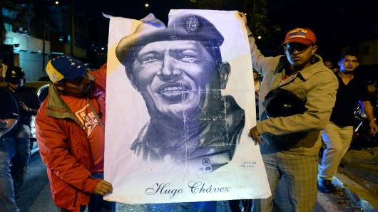 Supporters of Venezuelan President Hugo Chavez hold an allusive poster while gathering in front of the Military Hospital in Caracas on March 5, 2013, after knowing of their leader's death.