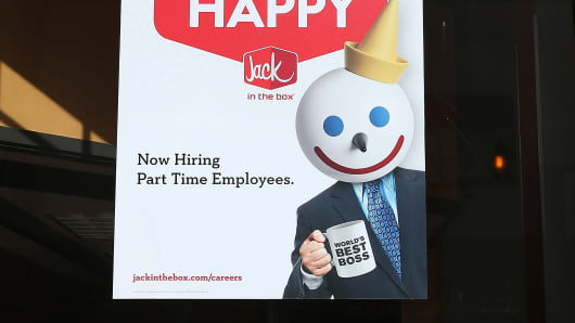 A sign advertising jobs is posted in the window of a Jack in the Box restaurant.