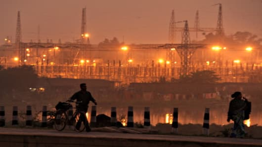 Pedestrians walk on a roadside past a power sub-station in the outskirts of Kolkata.