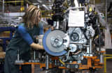 A worker builds an engine on the Ford assembly line.
