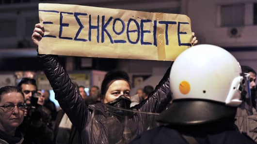 "A woman holds a banner that reads ""rise up"" in front of police as they attempt to disperse protesters in front the Greek parliament on March 10, 2013 in Athens."