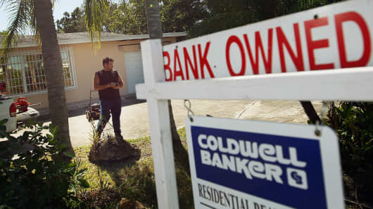 The yard around a foreclosed home is maintained by a bank-hired worker in Miami.