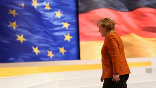 German Chancellor Angela Merkel,  walks past flags of the European Union and Germany.