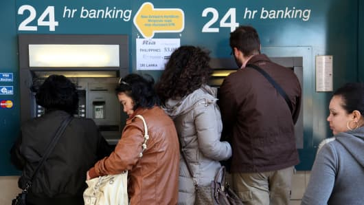 People withdraw money from an ATM in the Cypriot capital Nicosia. The Cyprus government postponed a planned emergency session of parliament on Sunday to debate a controversial EU bailout.