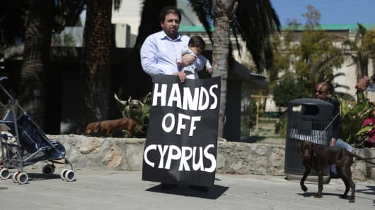 Cypriots protest outside the parliament building in Nicosia.