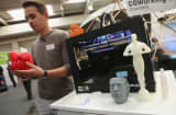 A host explains various objects created from molten plastic and a MakerBot 3-D printer at the 2013 CeBIT technology trade fair.