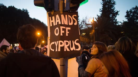 Demonstrators protest the bank deposit tax plan outside the Cypriot parliament on Tuesday.