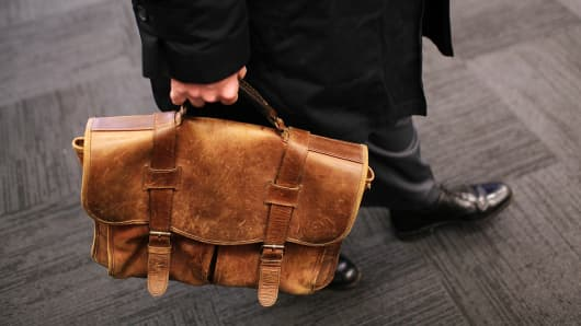A job seeker carries a worn briefcase at the Green Jobs and Entrepeneurship Fair in Berkeley, California.