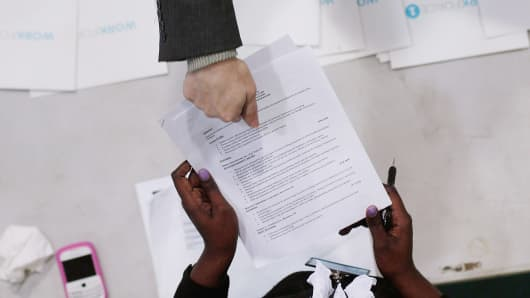 A job-seeker (top) hands his resume to Candice Perkins, a representatvie of Workforce1 during a 'Work Search' event aimed at older unemployed people in New York City.