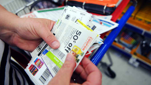 A woman sorts through coupons while shopping in California, Md.