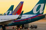 A Southwest Airlines Co. plane stands between two AirTran Airways Inc. planes at Hartsfield-Jackson International Airport in Atlanta, Georgia, U.S.