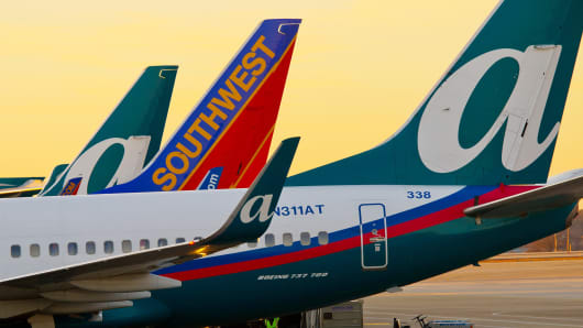A Southwest Airlines plane stands between two AirTran Airways planes at Hartsfield-Jackson International Airport in Atlanta.