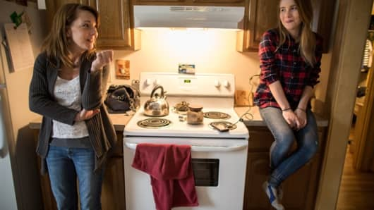 Tara Simons, left, and her daughter Alexis talk in their kitchen in West Hartford, Conn.