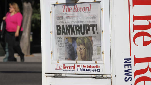 A pedestrian walks by a newspaper rack displaying the headline 'Bankrupt!' last summer in Stockton, Calif.