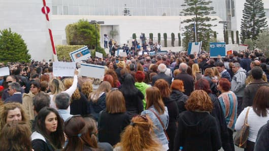 "Bank of Cyprus employees move demonstration from their headquarters to the Central Bank of Cyprus (the buildings are next door to each other).  They chanted ""resign, resign, resign"" - calling for the Governor of the Central Bank to step down."